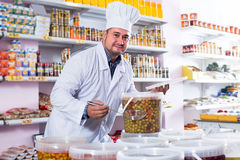 Male staff standing near containers with olives. Shop staff standing near containers with olives in flavoured brine Royalty Free Stock Photos