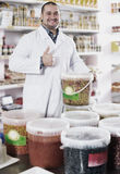 Male staff standing near containers with olives. Shop male staff standing near containers with olives in flavoured brine Royalty Free Stock Photo