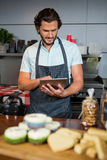 Male staff using digital tablet at counter. In coffee shop Royalty Free Stock Photography