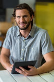 Male staff using digital tablet in grocery shop. Portrait of male staff using digital tablet in grocery shop Stock Photos