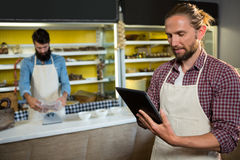 Male staff using digital tablet near meat counter. In market Stock Photo