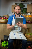 Male staff using digital tablet at organic section in market. Smiling male staff using digital tablet at organic section in market Royalty Free Stock Photos