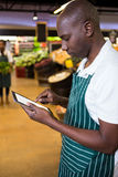 Male staff using digital tablet in organic section. Of supermarket Stock Images