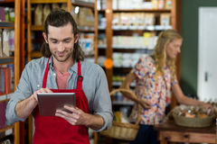 Male staff using a digital tablet. In supermarket Royalty Free Stock Image