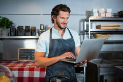 Male staff using laptop at counter. In coffee shop Royalty Free Stock Image