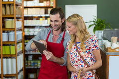 Male staff and woman looking at digital tablet. Male staff and women looking at digital tablet in supermarket Stock Photography