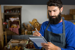 Male staff writing on notepad at counter. In bakery shop Royalty Free Stock Photo