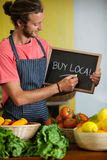 Male staff writing on slate board in organic section. Of supermarket Stock Images