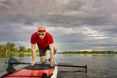 Male stand up paddler on lake. Senior male paddler starting his workout on  stand up paddleboard, a local lake in Colorado under cloudy sky Royalty Free Stock Images