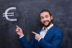 Male standing in front of blackboard background. Charismatic handsome man with beard  points to the euro symbol Royalty Free Stock Photo
