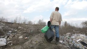 Male standing on the hill at garbage dump site. Back view of mature homeless man in dirty t-shirt standing on the hill at garbage dump with bin bags in hand stock footage