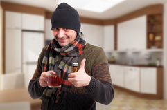 Male standing indoors with tea and pills Stock Photos