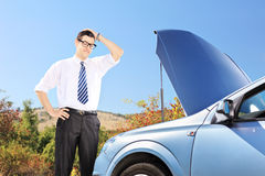 Male standing near a broken car and thinking what to do. Young male standing near a broken car and thinking what to do Royalty Free Stock Images