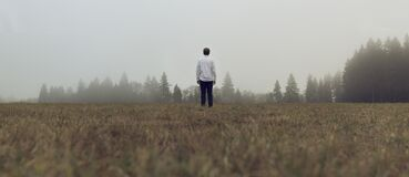 Male Standing in Open Field by Trees Royalty Free Stock Photo