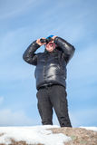 Man standing on the rock and looking at binoculars Royalty Free Stock Photo