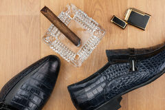 Male still life, classic men's shoes and a cigar in an ashtray. Can use as background Royalty Free Stock Photography