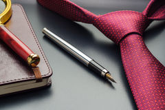 Male still life. A fountain pen with a notebook lies on a tie.  Royalty Free Stock Images