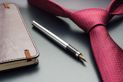 Male still life. A fountain pen with a notebook lies on a tie.  Royalty Free Stock Image