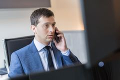 Businessman talking on mobile phone while watching charts and data analyses on multiple computer screens. Male stock broker talking on mobile phone while royalty free stock image
