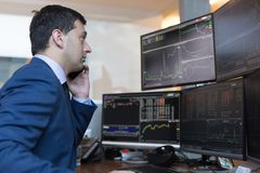 Stock broker trading online watching charts and data analyses on multiple computer screens. Male stock broker trading online watching charts and data analyses stock photos