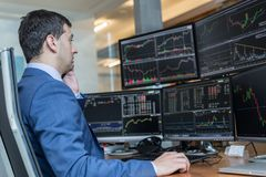 Stock broker trading online watching charts and data analyses on multiple computer screens. Royalty Free Stock Images