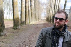 Male street fashion music. Bearded trendy handsome young man walking in the park in spring Royalty Free Stock Photography