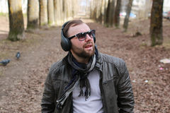 Male street fashion music. Bearded trendy handsome young man walking in the park in spring Royalty Free Stock Photos