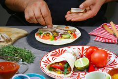 Male street vendor hands in gloves make taco. Mexican cuisine snacks, fast food of commercial kitchen royalty free stock image