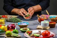 Male street vendor hands making taco. Mexican cuisine snacks, cooking fast food for commercial kitchen. concept cooking recipe stock photo