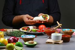 Male street vendor hands making taco. Mexican cuisine snacks, cooking fast food for commercial kitchen royalty free stock image