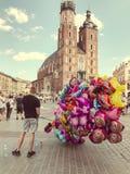 Male street vendor sells colorful popular cartoon character helium balloons. Krakow, Poland - July 29, 2017 : Male street vendor sells colorful popular cartoon Royalty Free Stock Image