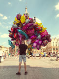 Male street vendor sells colorful popular cartoon character helium balloons. Krakow, Poland - July 29, 2017 : Male street vendor sells colorful popular cartoon Royalty Free Stock Photography