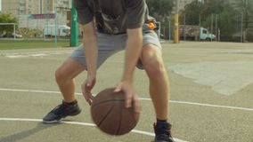 Male streetball player bouncing the ball on court. Closeup of male streetball player bouncing the ball and dribbling against defender on bascketball court during stock footage