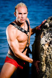 Male stripper. Fashion shot of a young man stripper posing on the beach in a sunny day Royalty Free Stock Photography