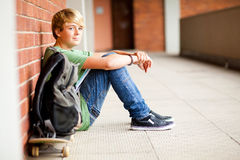 Male student. Cute male high school student sitting on floor Stock Photography