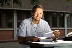 Male student. Close up of a male african college male student man reading books under the sun outdoors Stock Photo