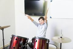 Smiling Boy Enjoying While Playing Drums In Class royalty free stock photo