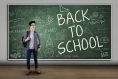 Male student back to school 1. Male college student standing in front of large blackboard with text of back to school Stock Photos