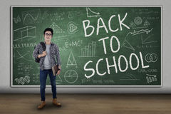 Male student back to school. Male college student standing in front of large blackboard with text of back to school Royalty Free Stock Photos