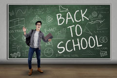 Male student back to school 2. Male college student standing in front of large blackboard with text of back to school Royalty Free Stock Photos