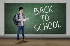 Male student back to school and use tablet. Full length of trendy student back to school and standing in the class while using a digital tablet Stock Photos