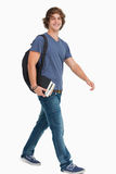 Male student with a backpack holding books. While walking against a white background Royalty Free Stock Photos