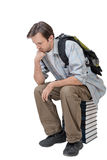 Male student with backpack sitting on the stack of books and thi. Nks - isolated on white Royalty Free Stock Photography