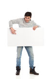 Male student with a banner. Young man holding pointing at banner. Full length studio shot isolated on white Royalty Free Stock Image