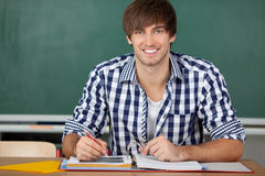 Male Student With Binder Sitting At Desk. Portrait of handsome young male student with binder sitting at desk against chalkboard Stock Images