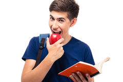 Male student biting apple and reading book. Happy male student biting apple and reading book isolated on a white background Stock Images