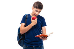 Male student biting apple and reading book. Isolated on a white background Royalty Free Stock Photography