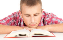 Male student with book. Leaning on the table, white background Royalty Free Stock Images