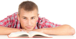 Male student with book. Leaning on the table, white background Royalty Free Stock Photography