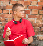 Male student with book. Leaning on the bricks wall Royalty Free Stock Images